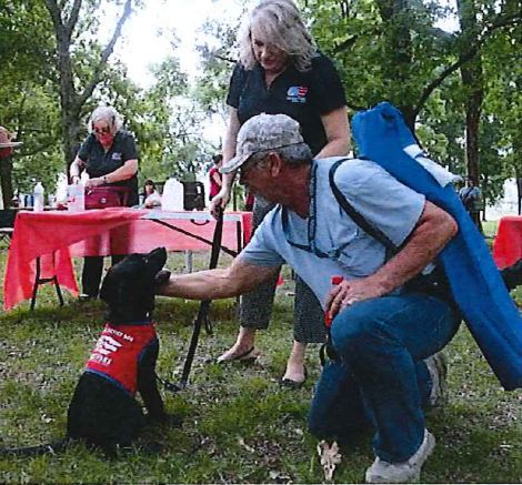 Leinbach Employees meet Tommy, a black lab dog currently being trained as a service animal for veterans.